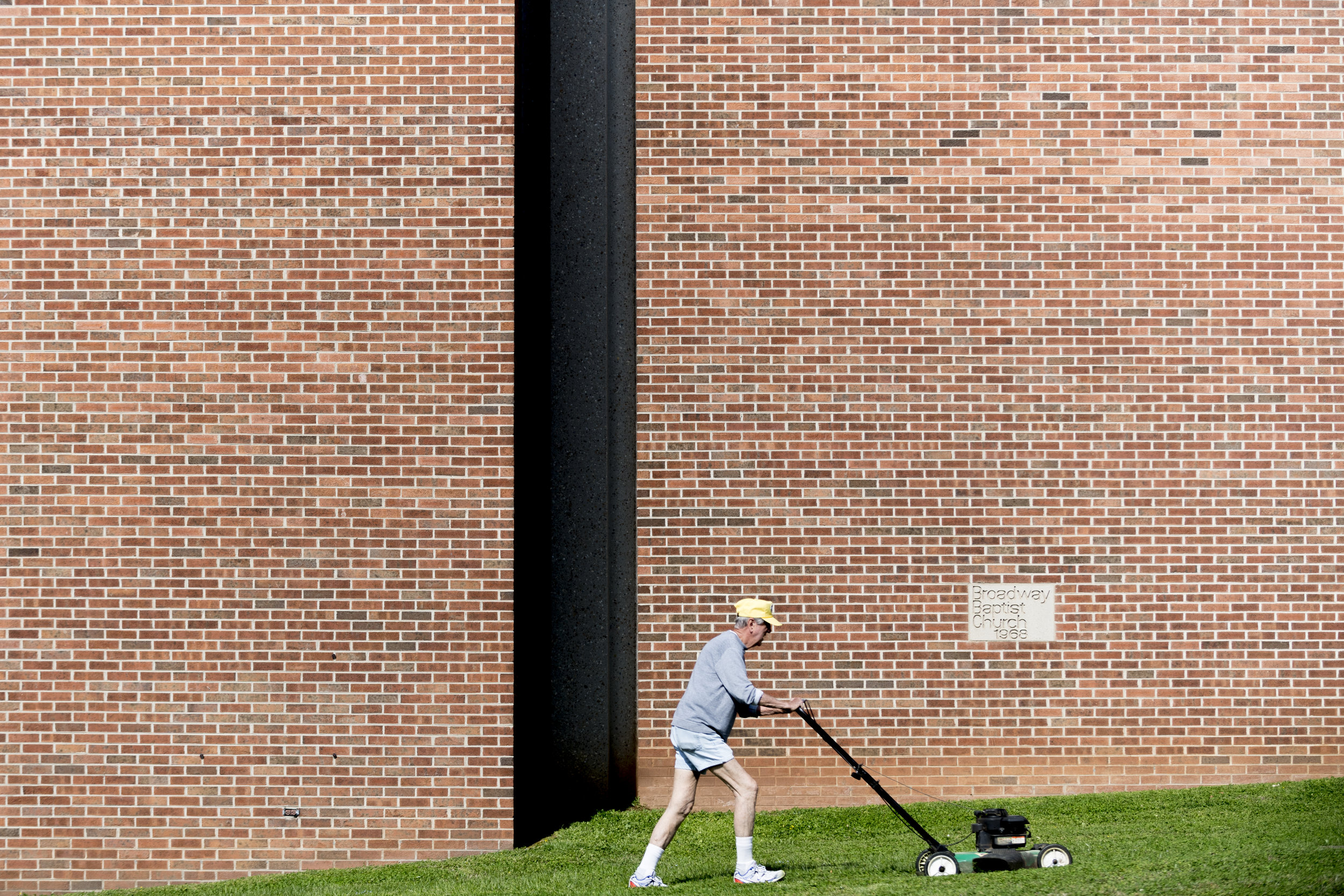 Richard  Bellah , of Knoxville, mows the lawn in front of Broadway Baptist Church in Knoxville. Bellah , who is a member of the church, has been doing landscaping for the church for eight years.