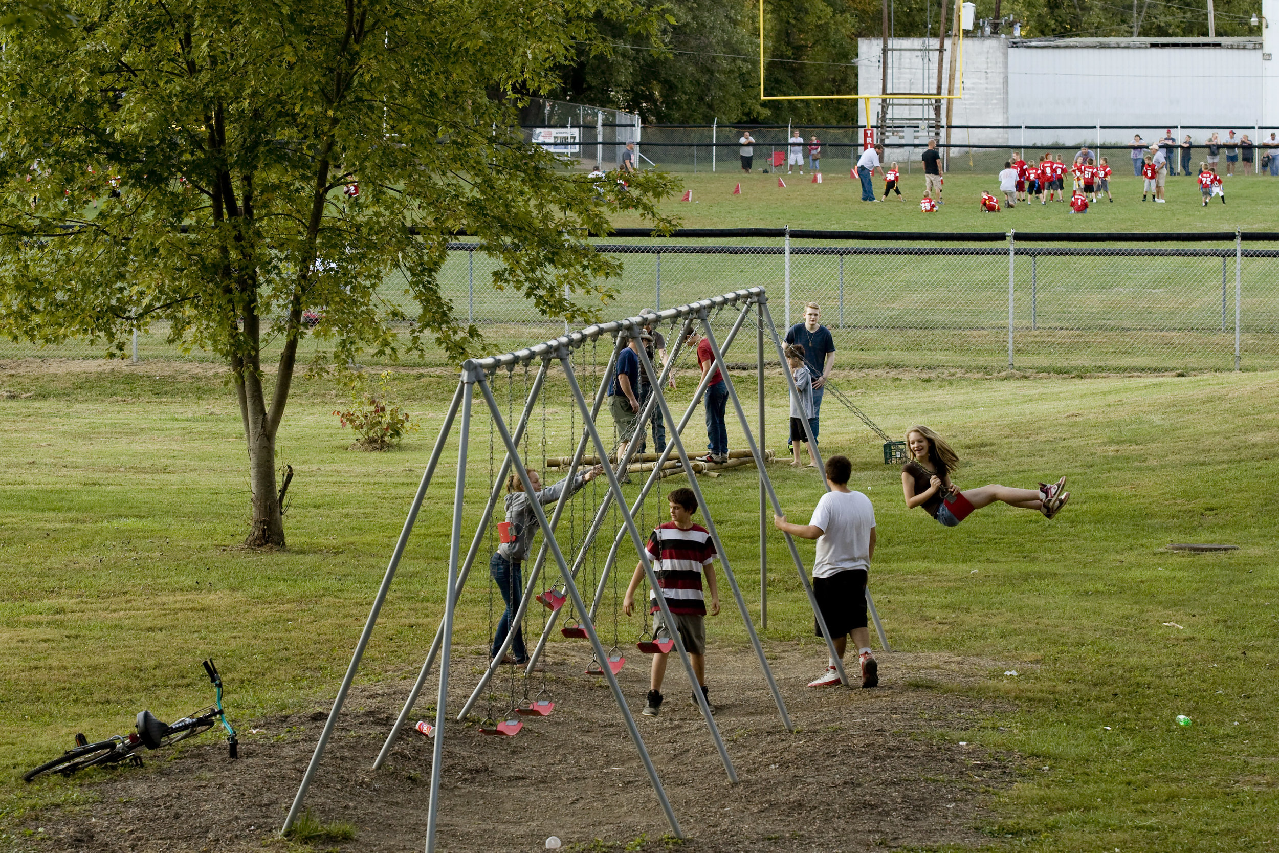 Children play on a swing set at Glouster Memorial Park next to Glouster Stadium in Glouster, Ohio, September 2014.