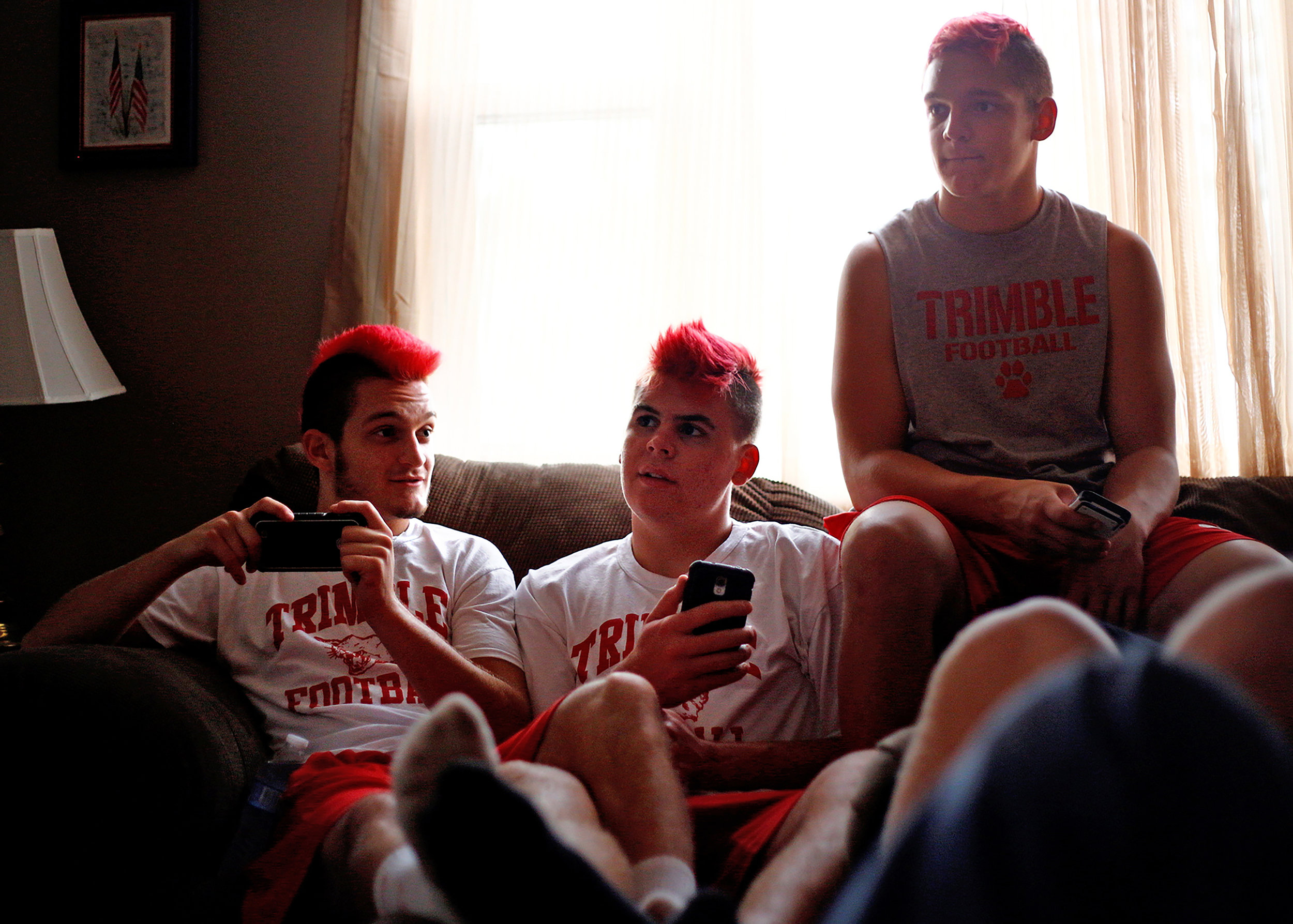 Austin Downs, Micah Couch and another teammate hang out at home after Trimble High School football practice in October 2014.