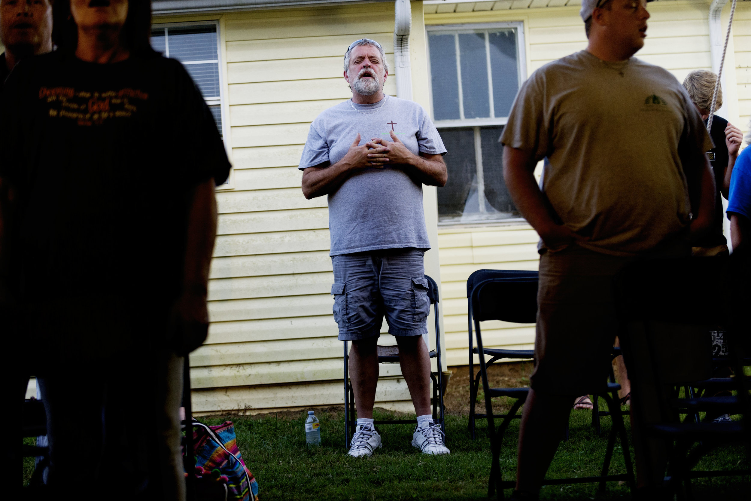 A church member sings along to a hymn during an outdoor church service at Dante Baptist Church in Knoxville, Tennessee on Wednesday, September 27, 2017.