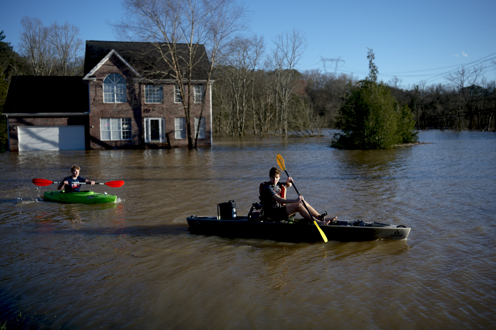 Truman Douglass and James Webster, both from Knoxville, pass by a flooded home next to the Sunoco on Ebenezer Road and Gleason Drive in Knoxville in February  2019.