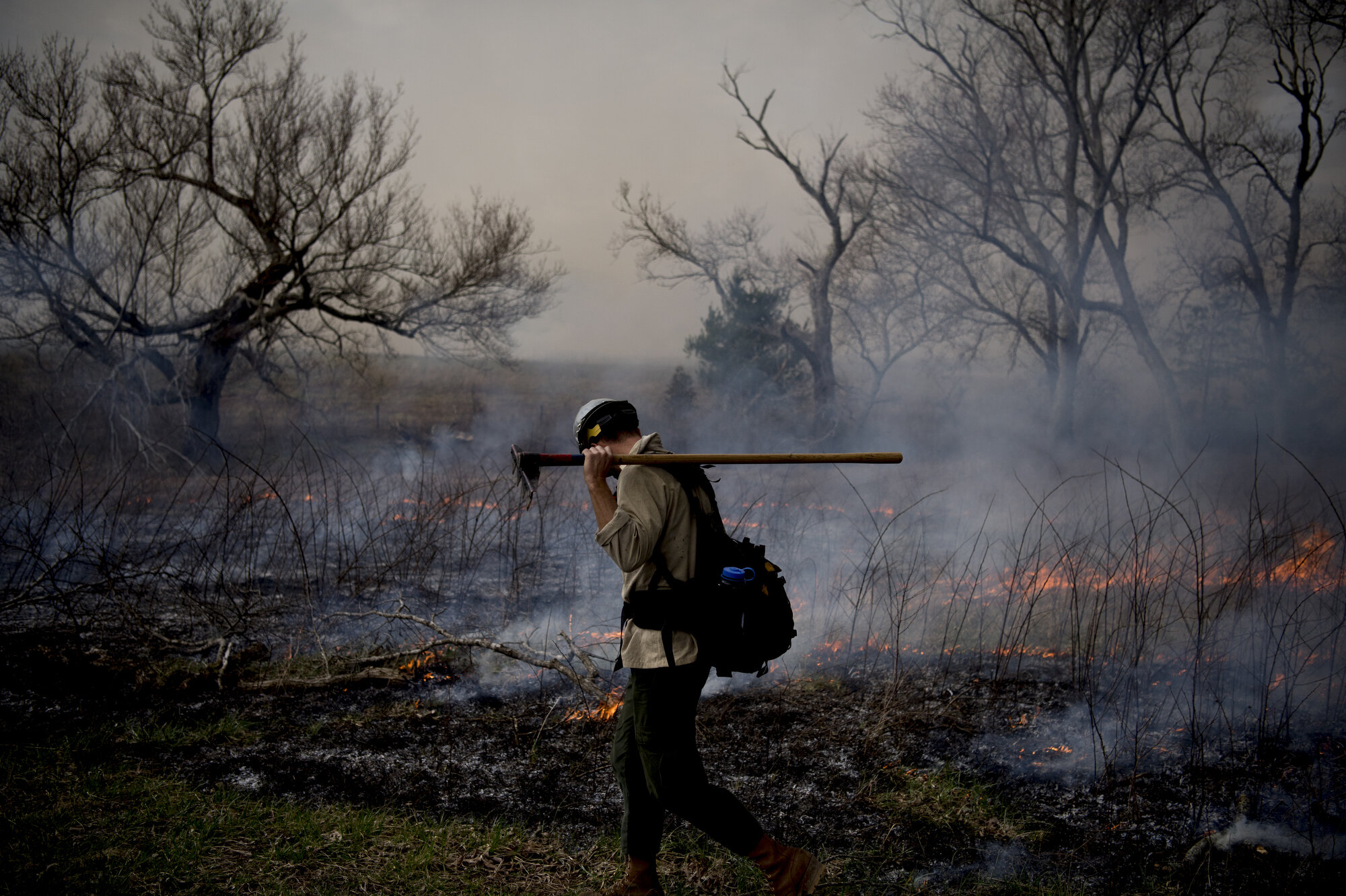 Jon Freeman, with Great Smoky Wildland Fire Module, monitors the behavior and direction of the fire during a prescribed burn in Cades Cove in Great Smoky Mountains National Park. Crews were burning roughly 440 aces to reduce shrub and tree intrusion, exotic plant species invasion and help maintain open meadows critical to the habitat of native wildlife.