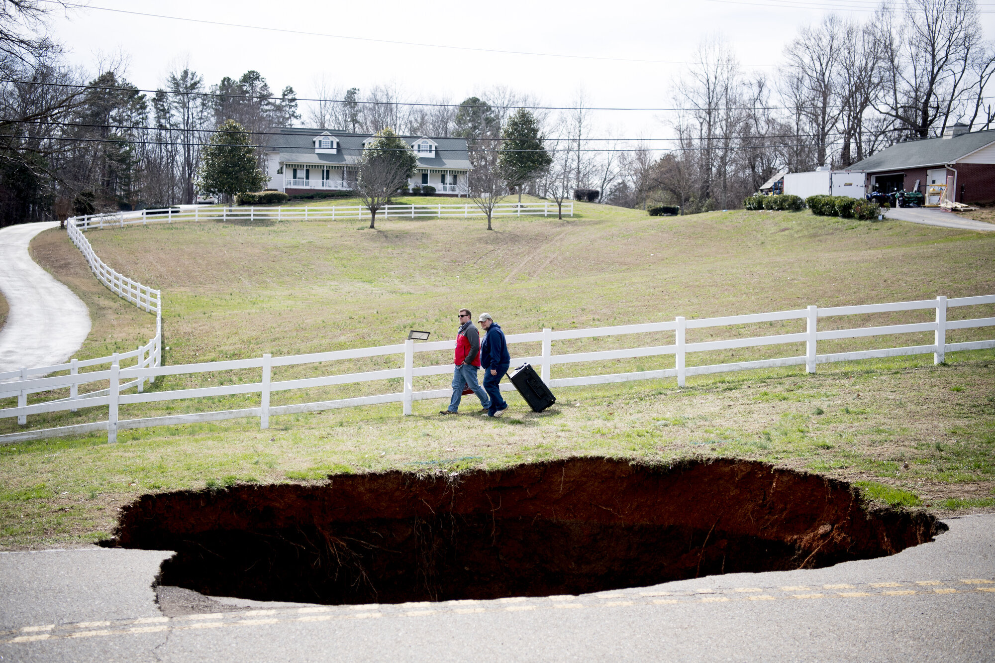 People walk past a large sinkhole on Greenwell Road in Powell, Tennessee. The sinkhole is estimated to be around 20 feet deep.