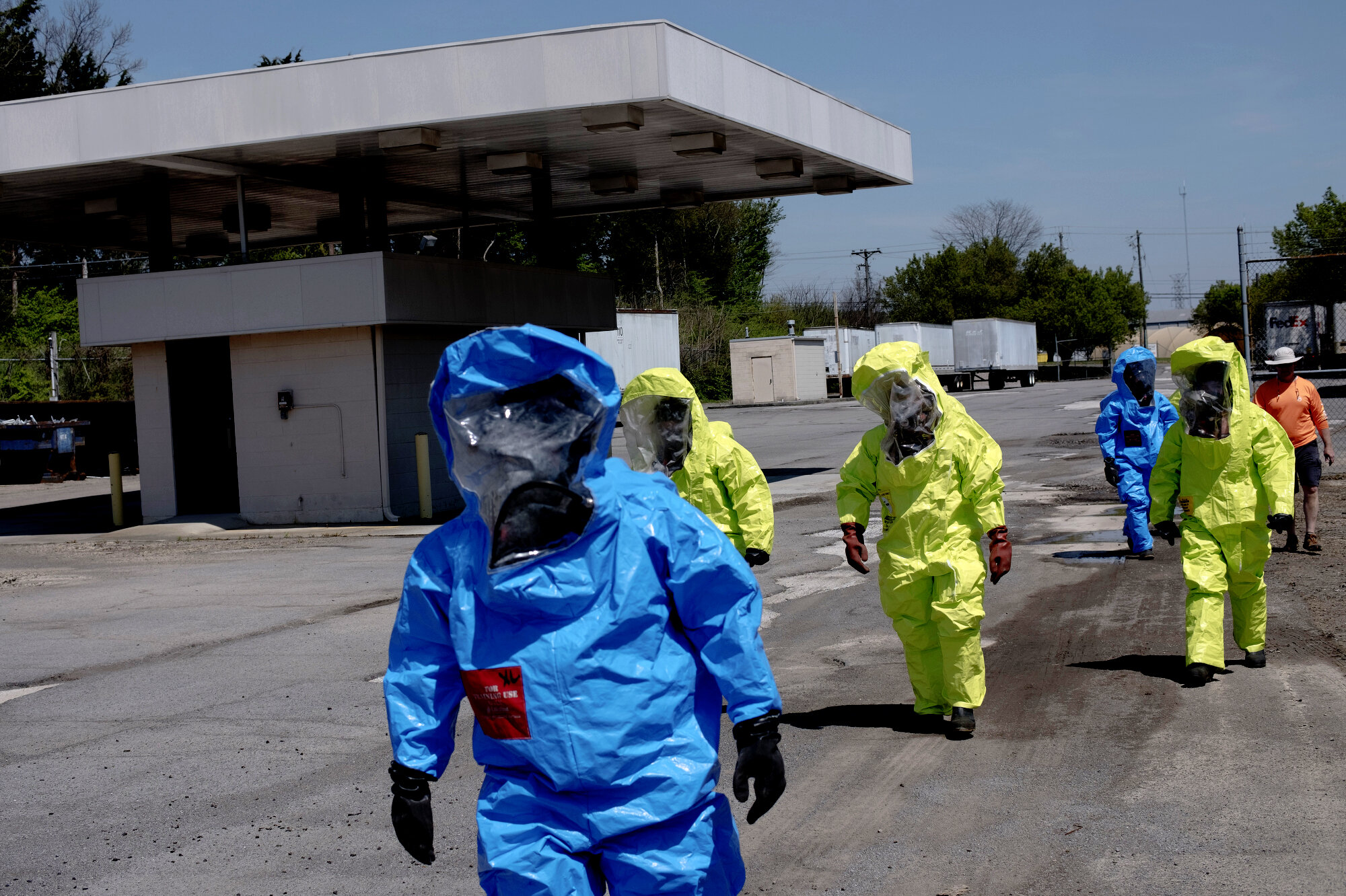 Hazardous material technicians walk in Class A hazmat suits during a field training session on remediating underground bombs and hazardous material in brown fields. Their training requires OSHA's 29 CFR 1910.120 certification, which private sector emergency responders obtain after successfully undergoing hazardous material response training.