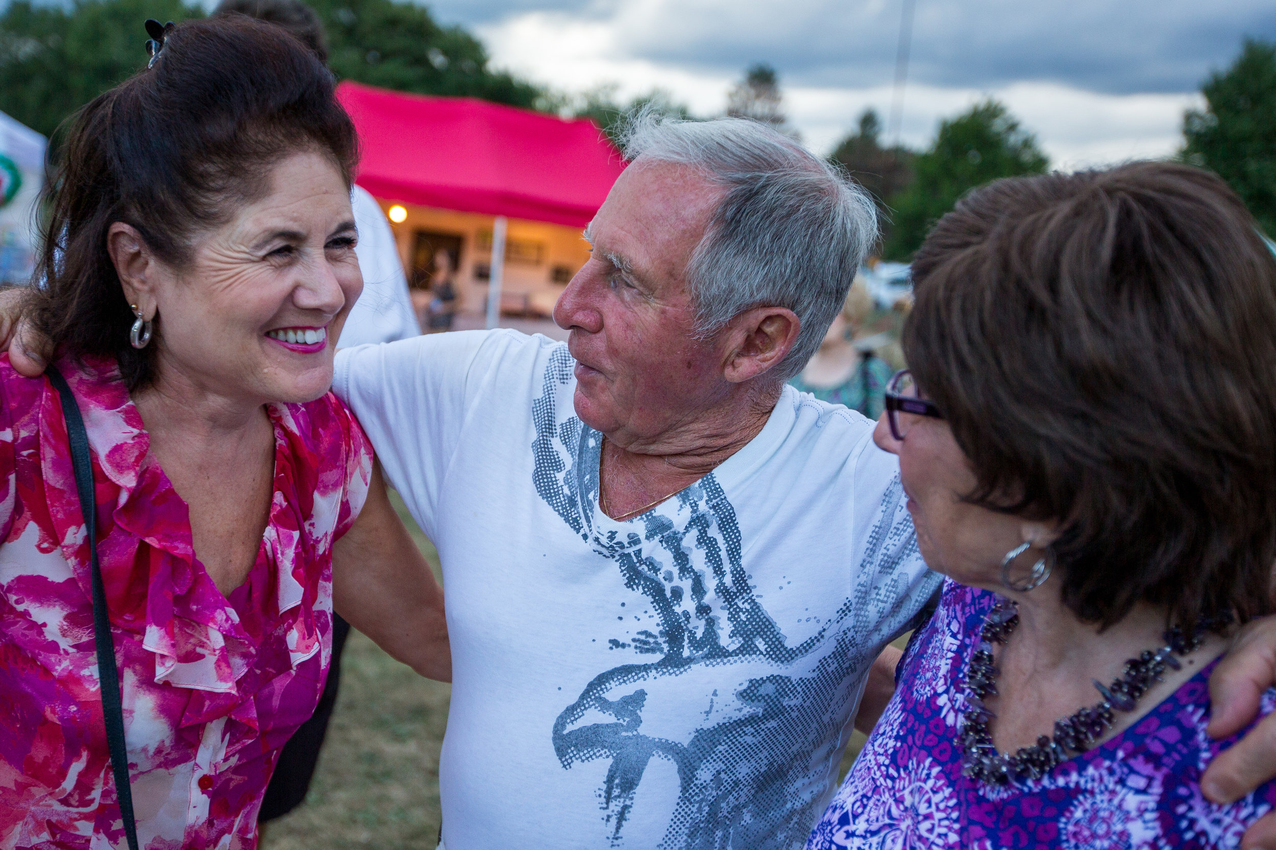 Henry Bufalini, center, hugs Carol Fox, left and Jeanne Smith at the 91st San Rocco Festa in Aliquippa on Saturday afternoon. The festival, which originated in the town of Patrica, Italy, took place over three days and featured live music, vendors, fireworks, a mass and the traditional baby doll dance on Sunday evening.