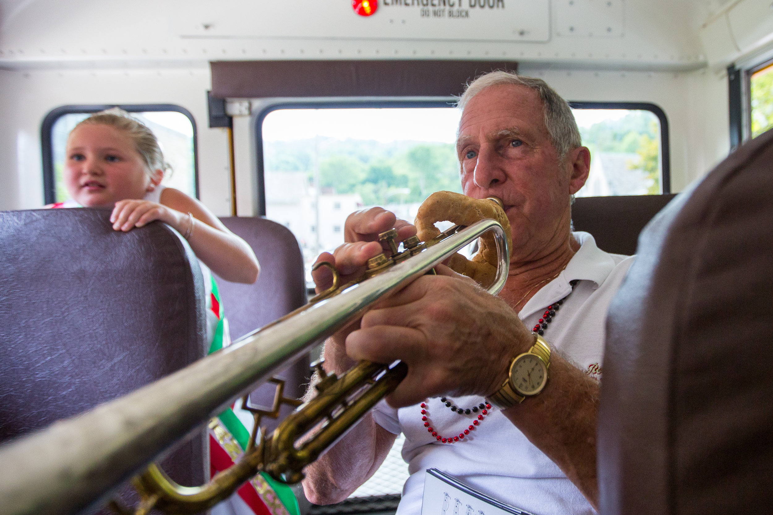 Henry Bufalini plays his trumpet in a school bus with other members of the San Rocco Festa Band as they drive from St. Titus Church to the beginning of the procession route on Sunday morning in Aliquippa. Thousands of people participated in the procession, which featured many families with family banners marching through the streets of Aliquippa with the San Rocco Festa Band and the statue of San Rocco.