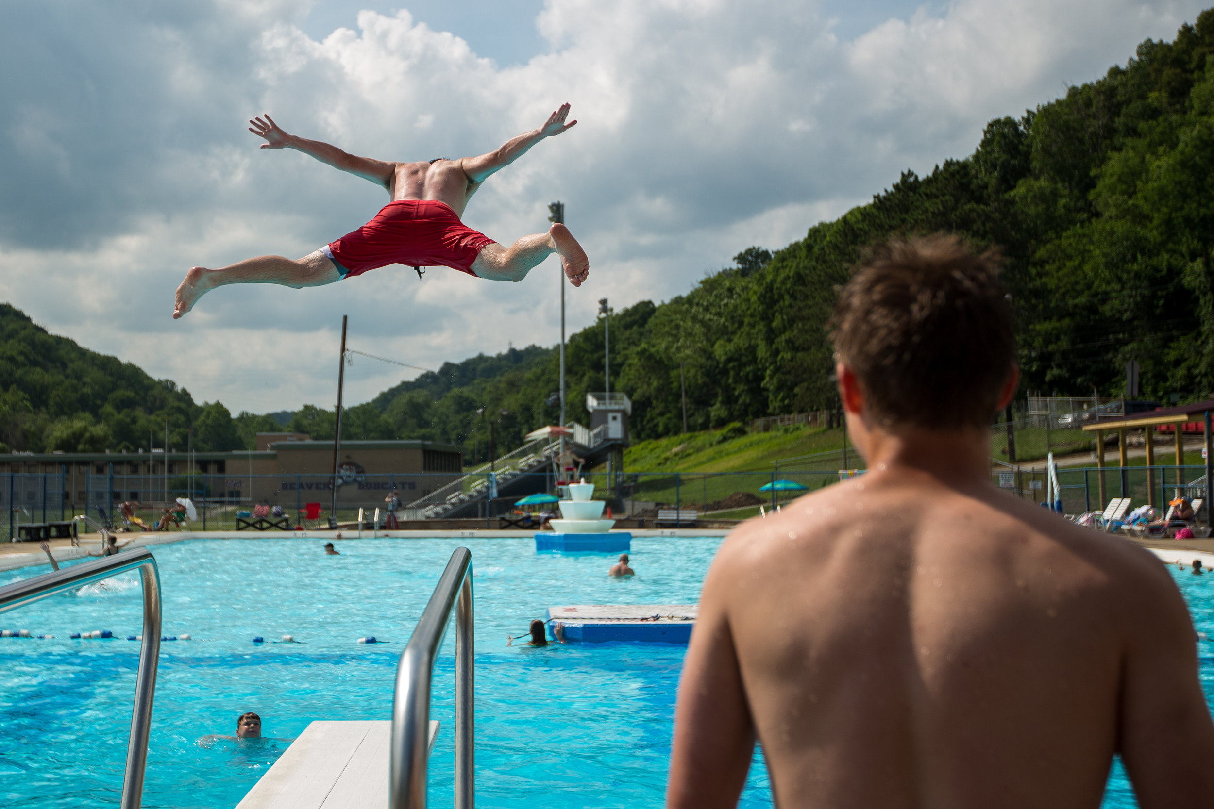 Patrick McGuckin, top left, jumps off of the diving board at the Beaver Pool white friend Zach Logan watches on Thursday afternoon.