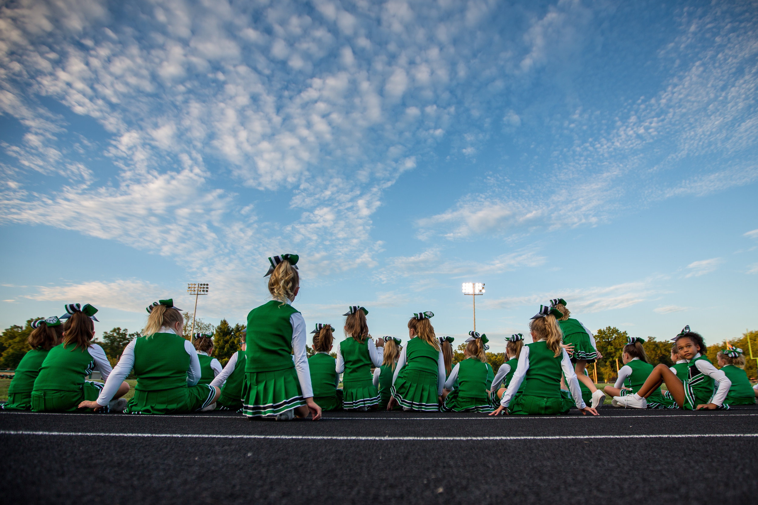 Participants of Twerp Cheer sit on the track while watching other cheerleaders perform at Riverside High School's Meet the Panthers pep rally on Thursday evening.