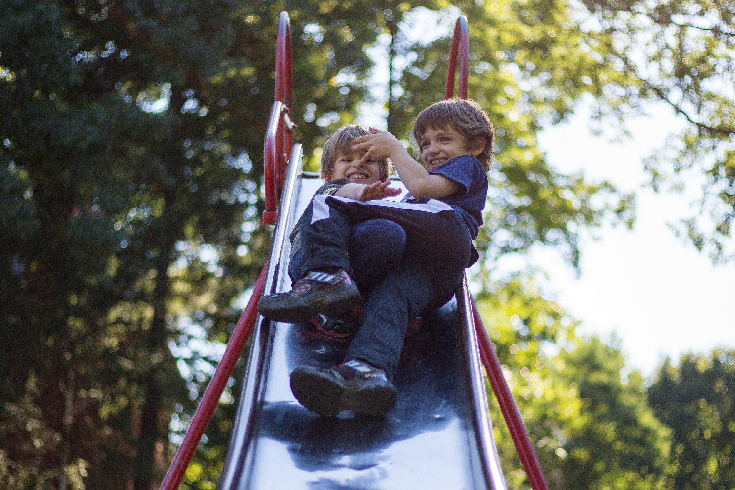 Gabriel Martella, 4, left and older brother Domynik, 8, play on the slide at Wayne Park in Beaver on Monday afternoon.