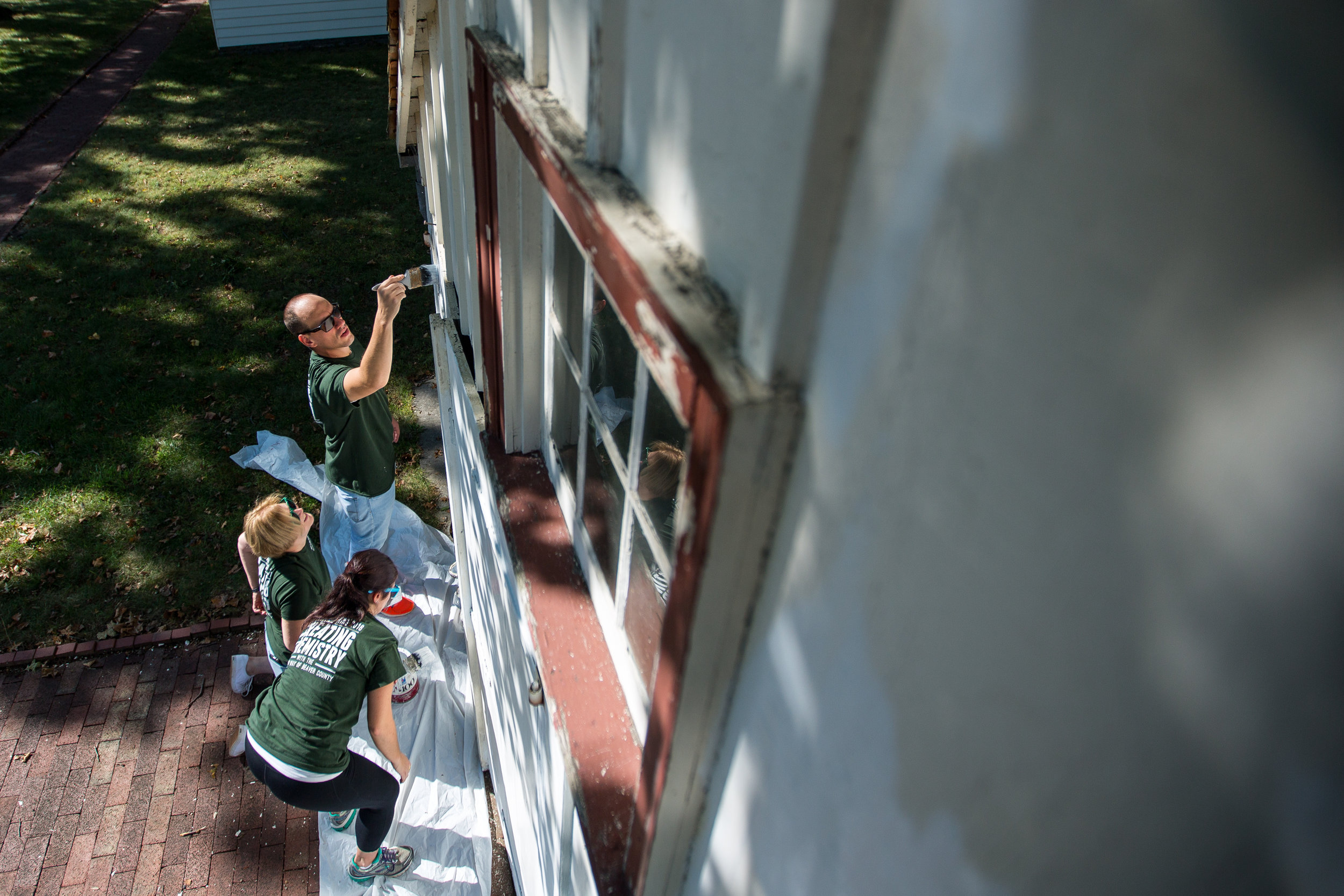 Matt Nosal, top, Susan McMullen and Jamie Telesz work on painting the side of the Blacksmith Shop at Old Economy Village on Wednesday morning. They were part of the United Way of Beaver County Day of Caring, bringing over 100 volunteers together to work at nonprofit organizations.