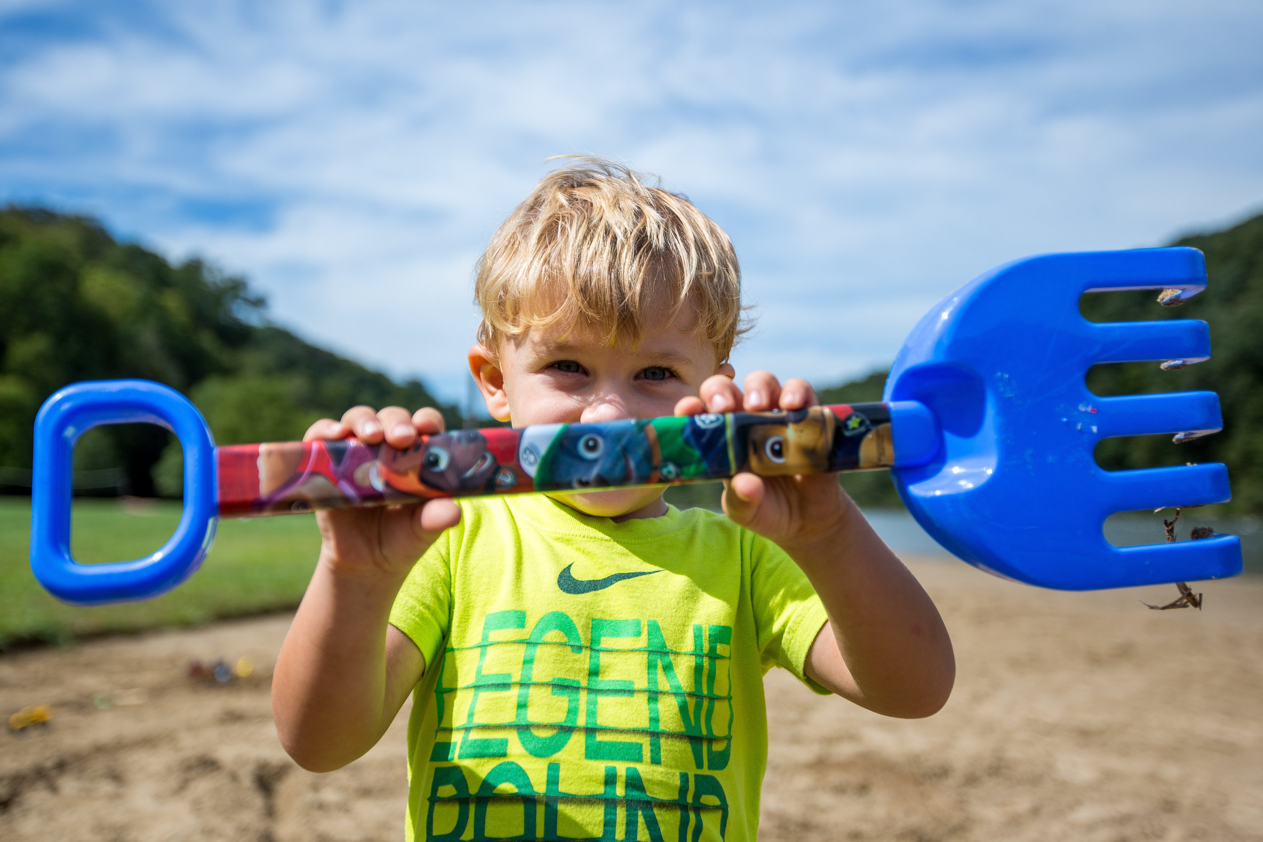 Jackson Slyder, 2, tries to hide behind his plastic rake at Raccoon Creek State Park on Thursday afternoon.