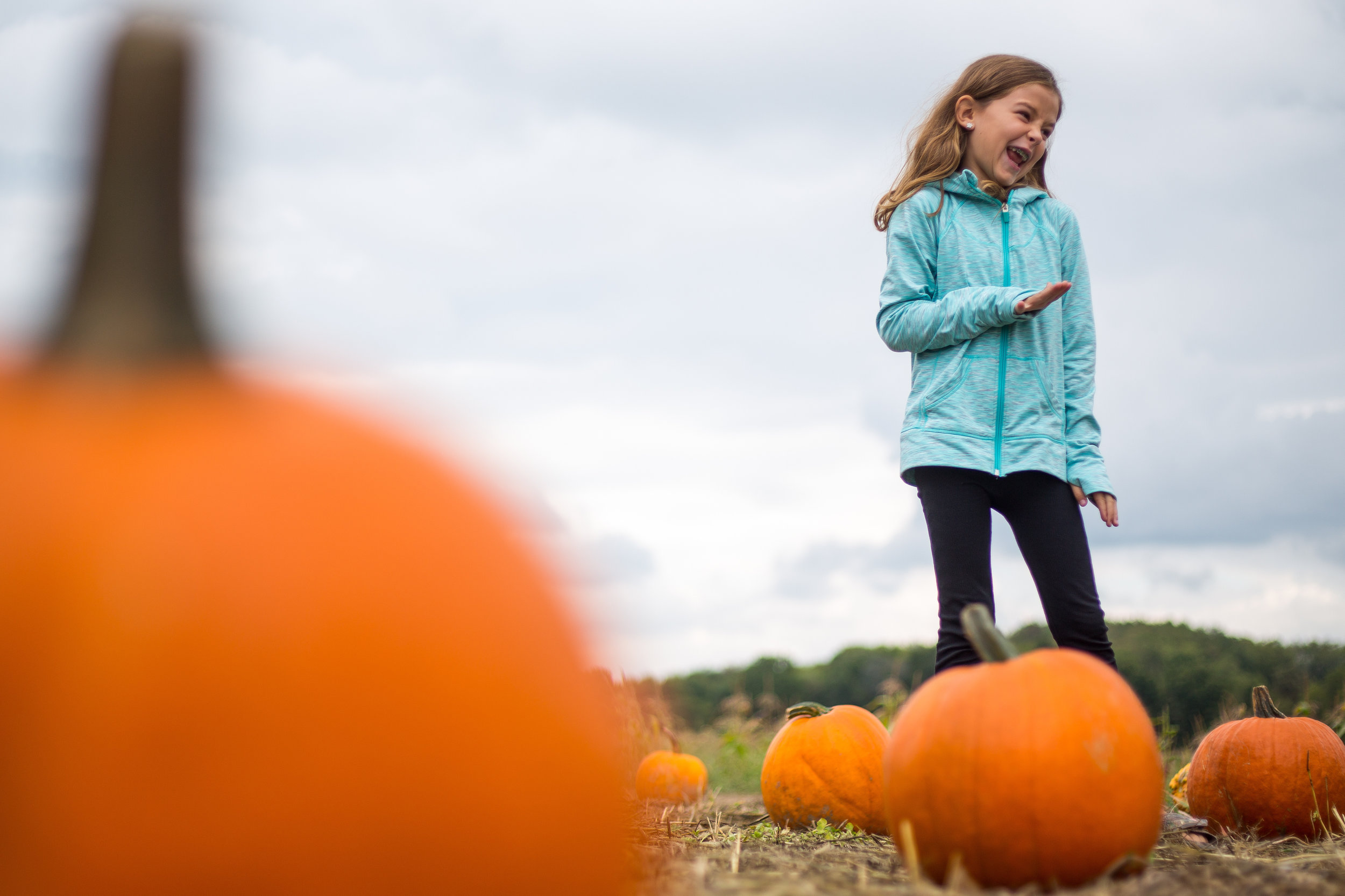 Ayla Sterner, 8, laughs as she finds the perfect pumpkin at Wise Farm in North Sweickley on Sunday afternoon.