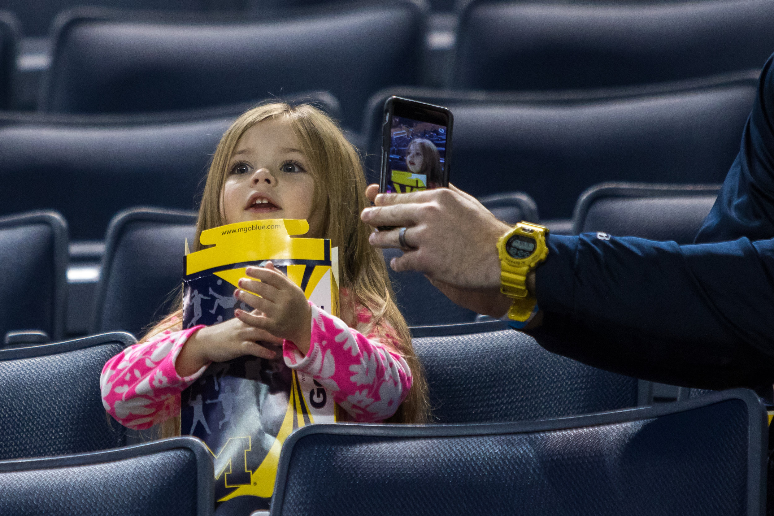 Dirk Roberts takes a photograph of his daughter Ava, 3, before tipoff between Michigan and Mount St. Mary's at the Crisler Center on Saturday, November 26, 2016. Matt Weigand | The Ann Arbor News
