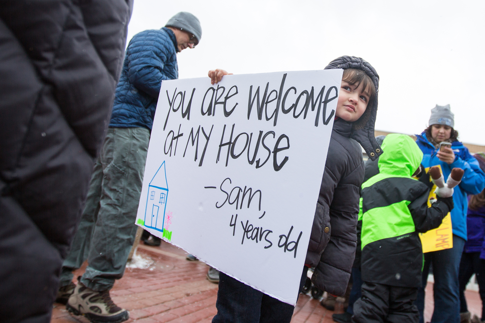 Sam Sussman, 4, holds a sign while attending an anti-immigration protest outside of the Federal Building in downtown Ann Arbor on Sunday, January 29, 2017. About 100 people attended the protest. Matt Weigand | The Ann Arbor News