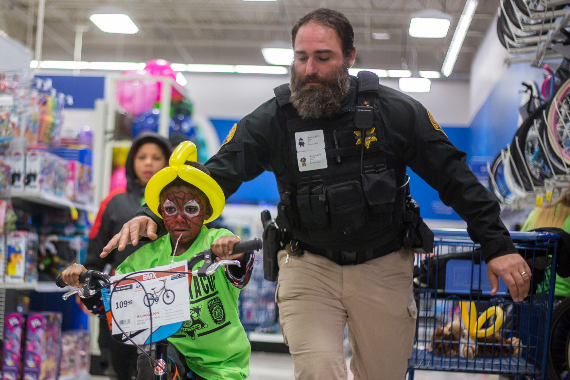 Washtenaw County Sheriff Deputy Buffa pushes Jametrick Woods, 6, on a bike at Meijer in Belleville during the Shop with a Cop on Wednesday, December 7, 2016. The shop with a Cop program paired 100 children with about 120 local police officers, sheriff deputies and volunteers for a $125 shopping trip a Meijer. Matt Weigand | The Ann Arbor News