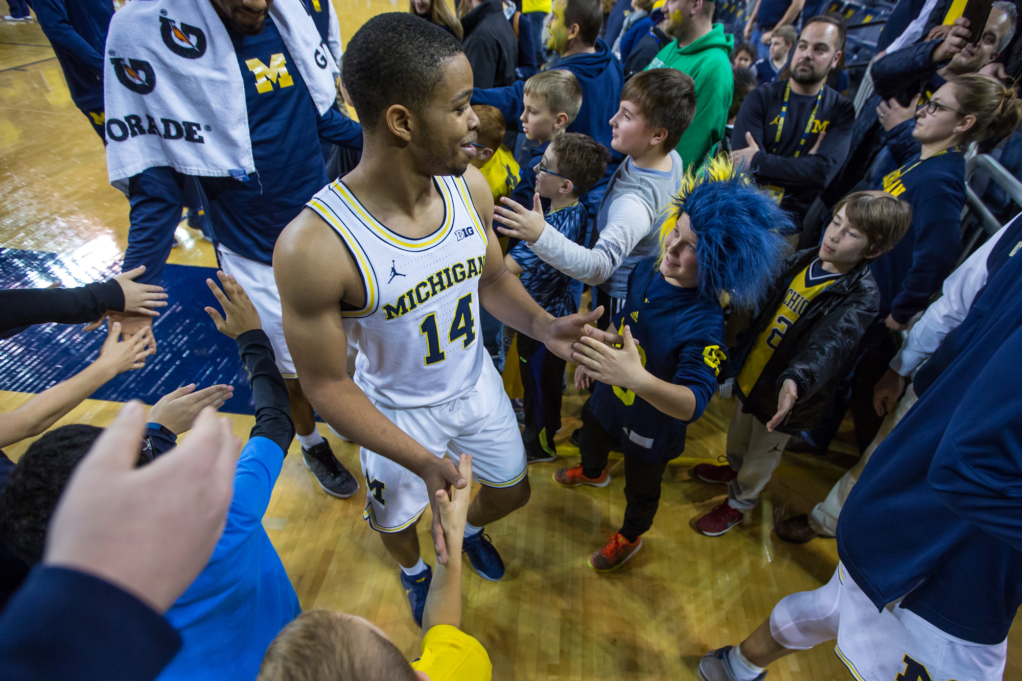 Michigan�s Fred Wright-Jones (14) shakes hands with young fans after the completion of play at the Crisler Center on Saturday, December 17, 2016. The Michigan Wolverines beat the Maryland Eastern Shore Hawks 98-49. Matt Weigand | The Ann Arbor News