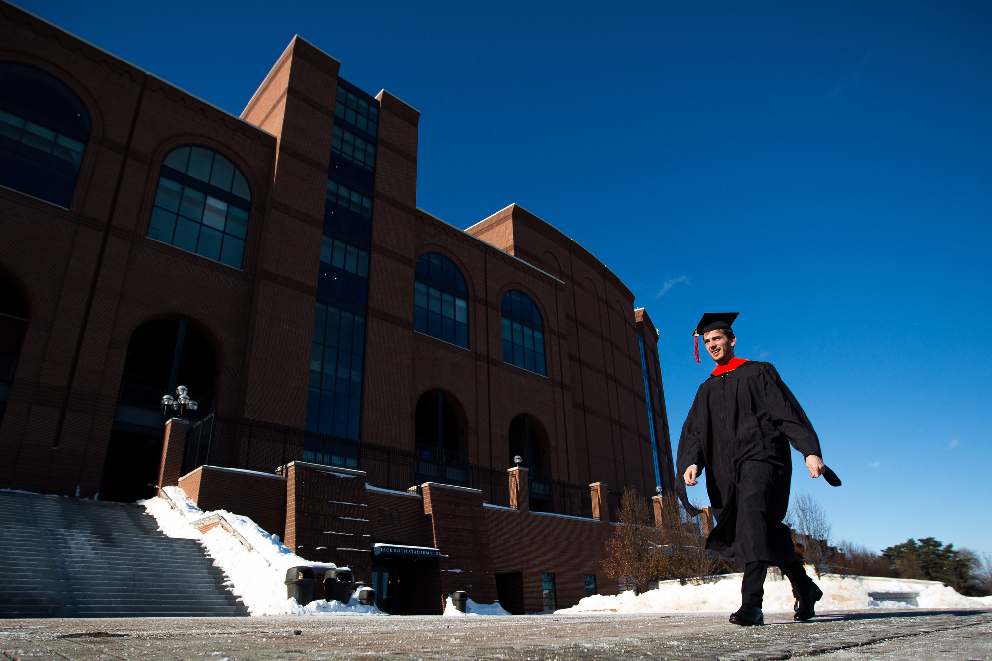 Florian Jule, graduating with a masters of science in aerospace engineering, walks past Michigan stadium before the University of Michigan winter commencement on Sunday, December 18, 2016. Jule and about 1,000 other students graduated at the Crisler Arena on Sunday. Matt Weigand | The Ann Arbor News