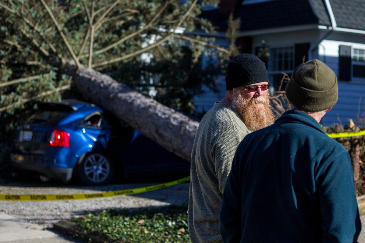 Homeowner Phillip Cartman, left, talks with neighbors after a large tree sits on the top of a car belonging to a nanny at Cartman's neighbors house near the corner of Packard Street and Granger Ave. after being toppled by high winds on Wednesday, March 8, 2017. Matt Weigand | The Ann Arbor News