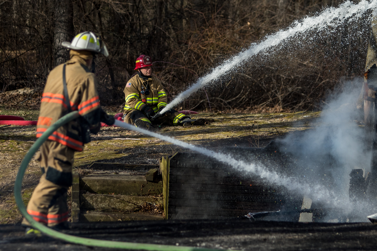 Two fire fighters work to extinguish a structure fire on Scully Road in Webster Township on Friday, March 10, 2017. The fire completely destroyed the home and a nearby field caught on fire. The cause of the fire is still under investigation. Matt Weigand | The Ann Arbor News