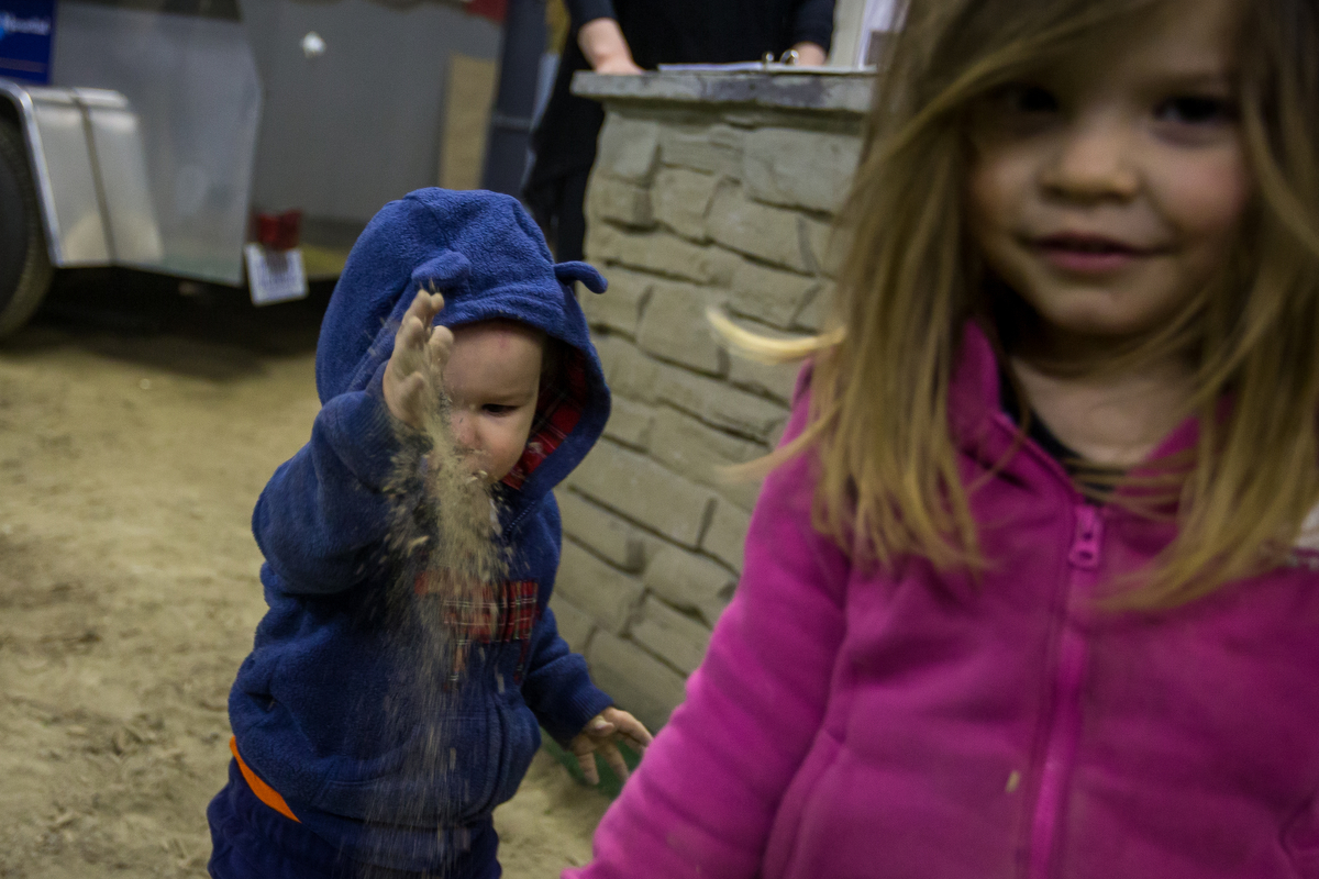 David Makowski, 1, throws dirt while playing with his sister Cynthia, 3, at The Home, Garden and Lifestyle Show at the Washtenaw Farm Council Grounds on Saturday, March 18, 2017. This year marked the 27th year of the show and hosted over 170 vendors. Matt Weigand | The Ann Arbor News