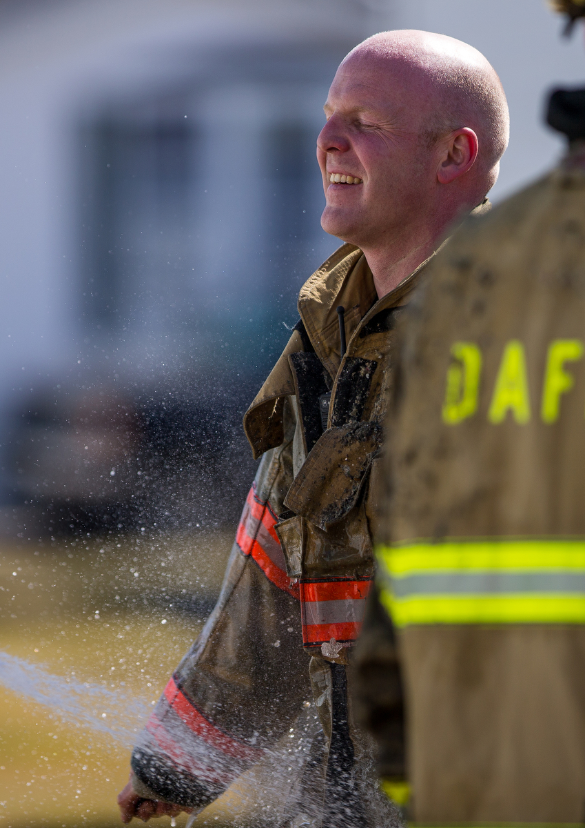 A fire fighter closes his eyes as a fellow fire fighter sprays him off after extinguishing a fire at a mobile home in Scio Farm Estates that caught fire on Thursday, March 23, 2017. The cause of the fire is under investigation. Matt Weigand | The Ann Arbor News