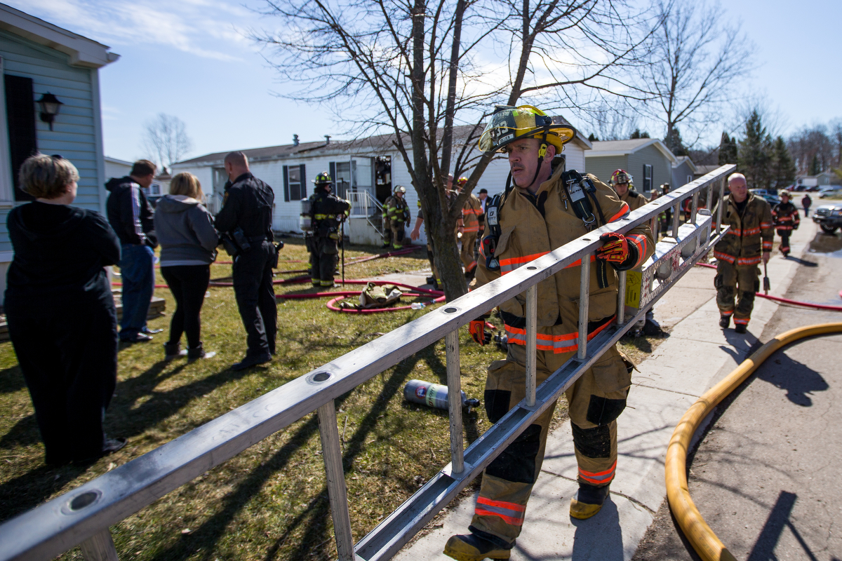 A fire fighter walks a ladder back to a fire truck after extinguishing a fire at a mobile home in Scio Farm Estates that caught fire on Thursday, March 23, 2017. The cause of the fire is under investigation. Matt Weigand | The Ann Arbor News