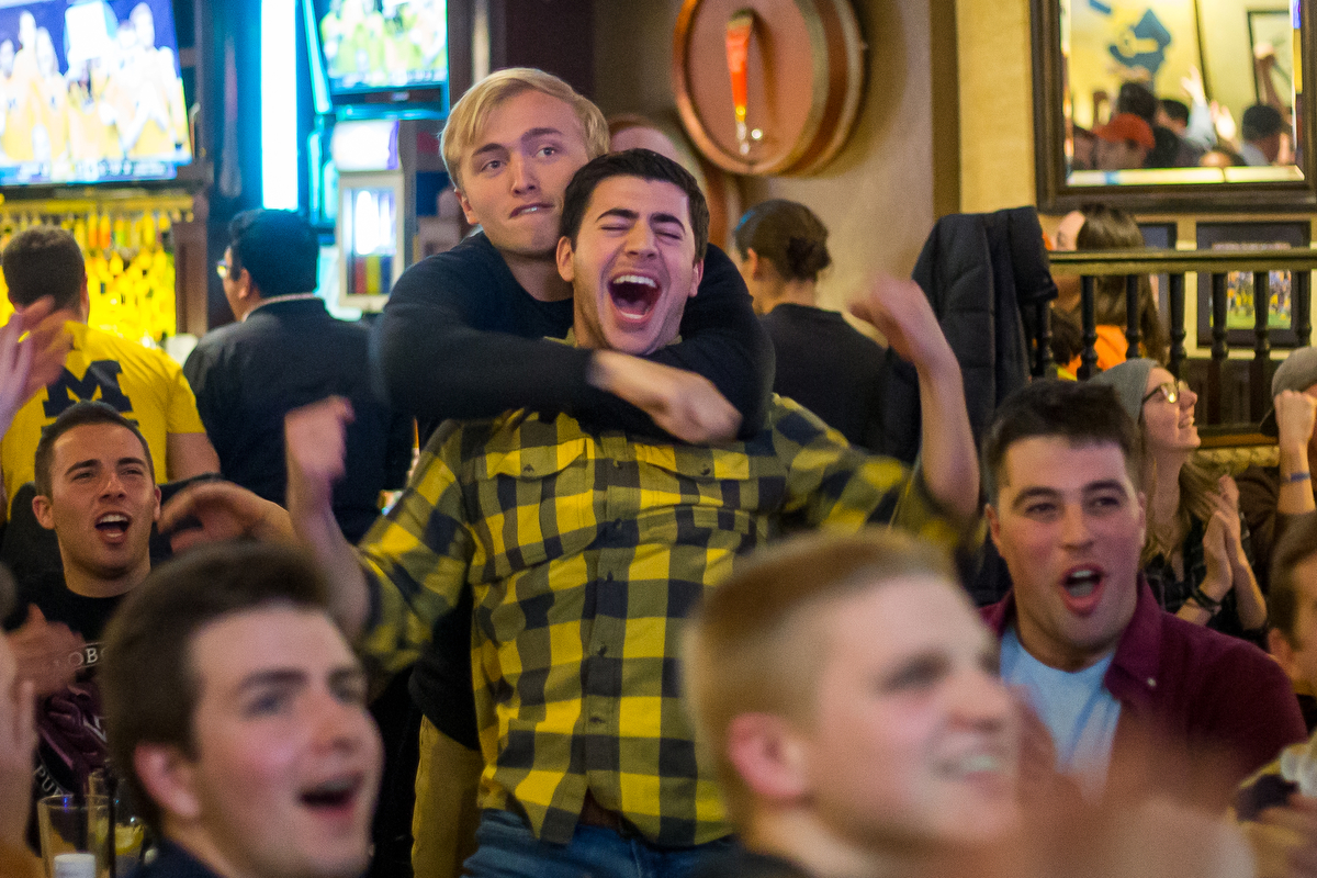 Alex Henderson, senior, back, hugs Brandon McCann, senior, as the Michigan and Oregon Sweet 16 game plays at the Blue Leprechaun on Thursday, March 23, 2017. The Michigan Wolverines lost to the Oregon Ducks 68-69. Matt Weigand | The Ann Arbor News