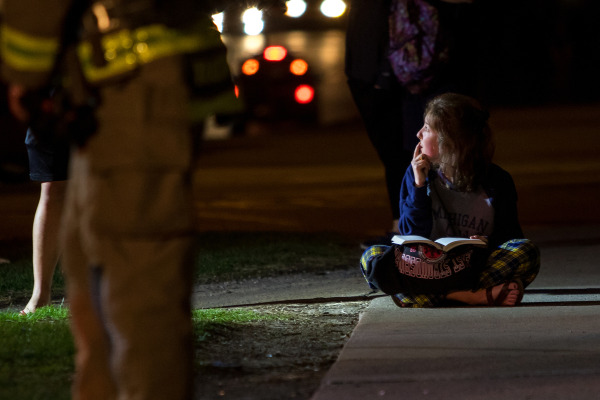 Meredith Mcphail, first year law student at the University of Michigan, studies outside of her apartment building at 607 Hill St. after a small fire was called to the Ann Arbor Fire Department at 8:13 p.m. on Monday, March 27, 2017. The fire was contained to one unit and was the result of a kitchen fire, according to Battalion Chief Randy Menard. Matt Weigand | The Ann Arbor News