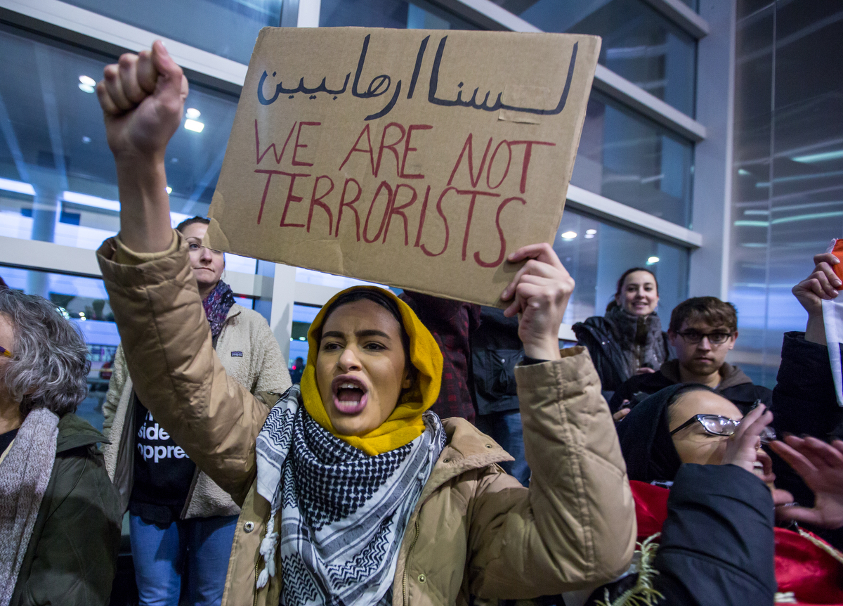 A woman participates with thousands in a protest against President Donald Trump and his new immigration policy at Detroit International Airport on Sunday, January 29, 2017.