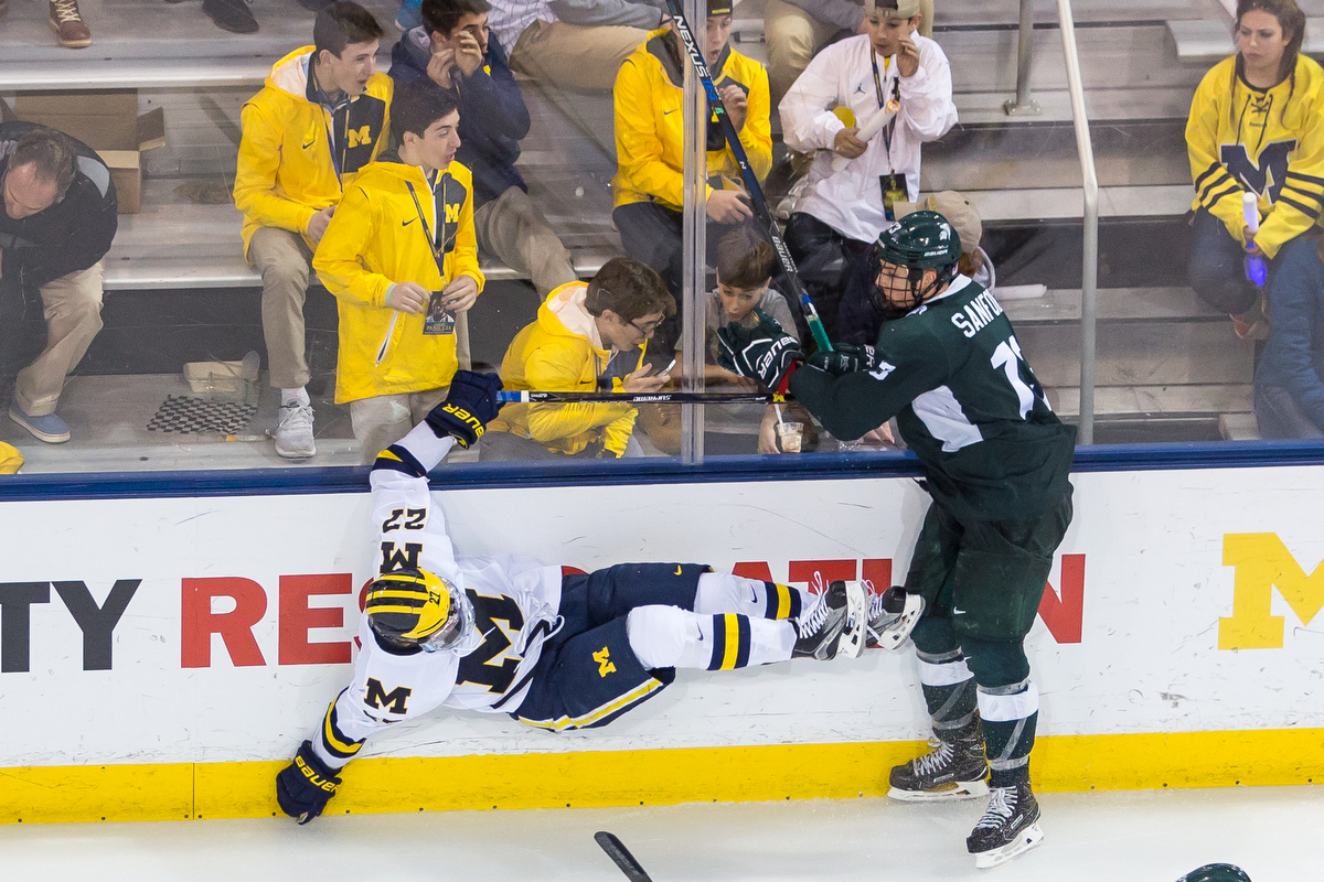 Michigan's Nicholas Boka (27) is thrown into the wall during the matchup against Michigan State at Yost Ice Arena on Saturday, February 11, 2017. The Michigan State Spartans beat the University of Michigan Wolverines 4-1.