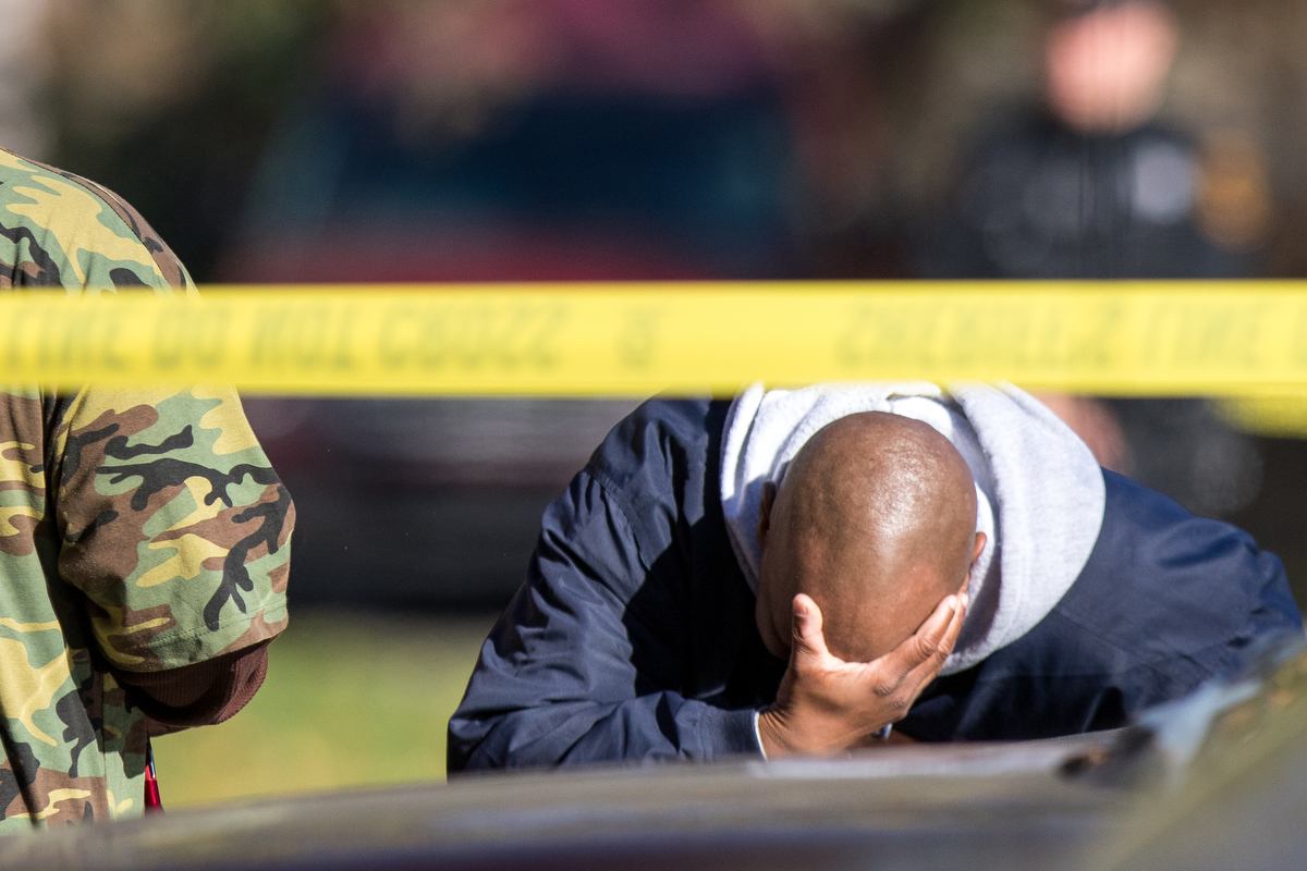 A man rests his head in his hands after talking to police outside of an apartment complex after a three-year-old was fatally shot on Sunday, November 13, 2016.