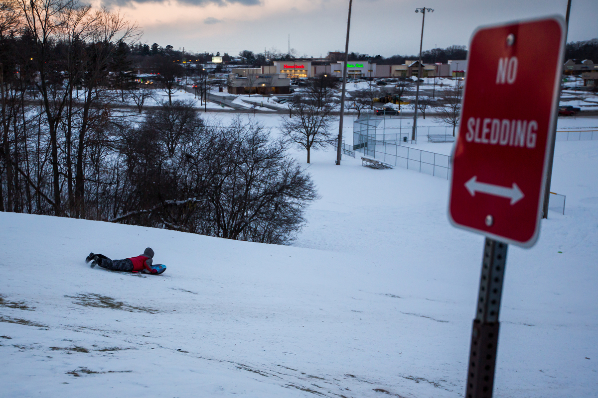 A young boy sleds down a hill at Veterans Memorial Park on Monday, December 12, 2016.