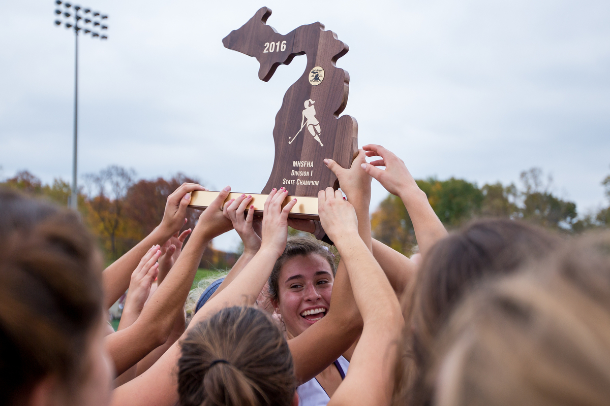Players from Pioneer High School hold up the MHSFHA Division I State Championship trophy after their win in the D1 State Field Hockey Championships against Dexter High School at Skyline High School on Saturday, October 29, 2016. Pioneer beat Dexter during seven-on-seven overtime.