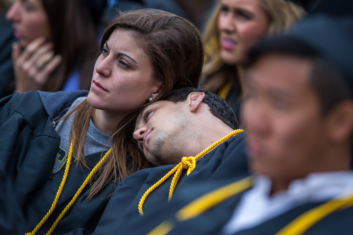 Two graduates rest their heads on each other during the 2017 University of Michigan spring commencement at Michigan Stadium on Saturday, April 29, 2017. Matt Weigand | The Ann Arbor News