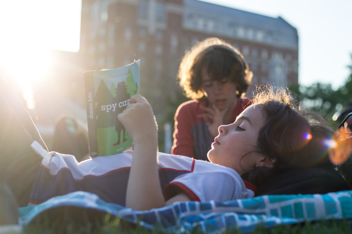 Levi Berg, nine, reads a book at Ingalls Mall for the opening night of Top of the Park, part of the Ann Arbor Summer Festival on Friday, June 9, 2017. The opening night featured yoga, multiple live music acts and food and drinks for all ages. Matt Weigand | The Ann Arbor News