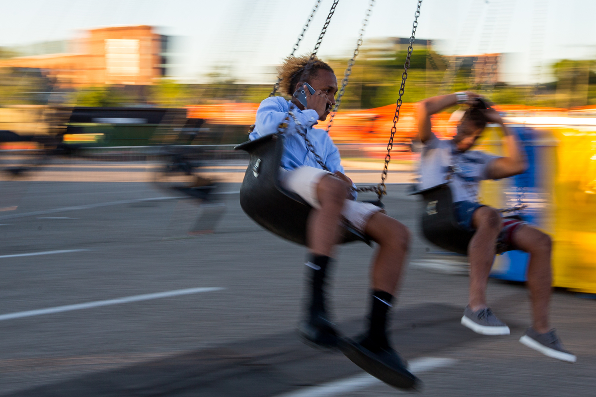 Elijah Beall talks on the phone while riding a ride during the opening day of the Ann Arbor Jaycees Carnival at Huron high School on Wednesday, June 21, 2017. The carnival runs from Wednesday to Sunday and over 30 rides and carnival games are available for all ages. Matt Weigand | The Ann Arbor News