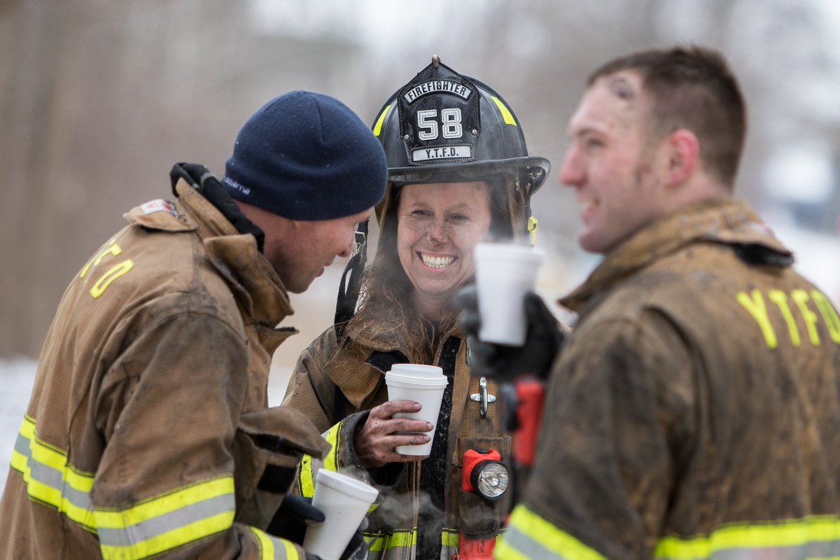 Maryanne Cleaver of the Ypsilanti Township Fire Department smiles with colleagues while drinking coffee after extinguishing a house fire at 9525 East Bemis Road in Ypsilanti Township on Sunday, January 29, 2017. The fire, which is still under investigation, was called in at about noon. Matt Weigand | The Ann Arbor News