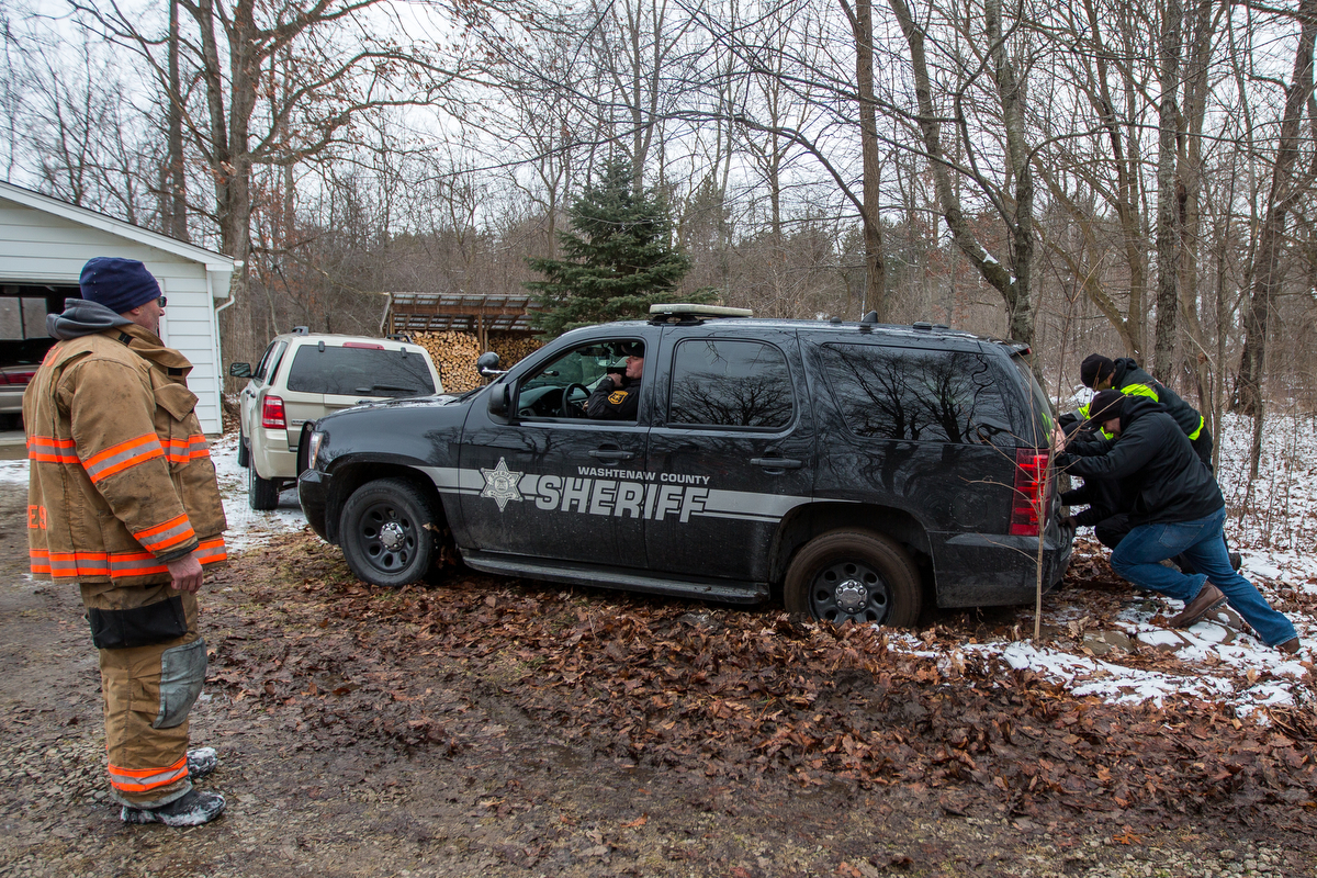 Employees of Belfor property restoration help push out a sheriff's patrol car after it got stuck in the mud after Ypsilanti Township fire fighters after extinguishing a house fire at 9525 East Bemis Road in Ypsilanti Township on Sunday, January 29, 2017. The fire, which is still under investigation, was called in at about noon. Matt Weigand | The Ann Arbor News