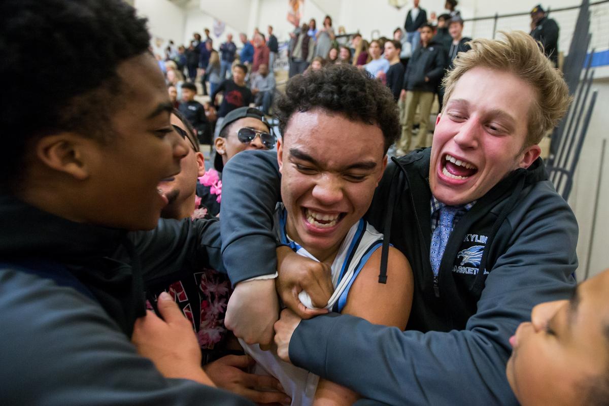 People surround and congratulate Brandon Wade (2), center, after he scored the game winning shot against Huron High School at Skyline High School on Friday, February 3, 2017. Skyline high School beat Huron high School 63-62. Matt Weigand | The Ann Arbor News