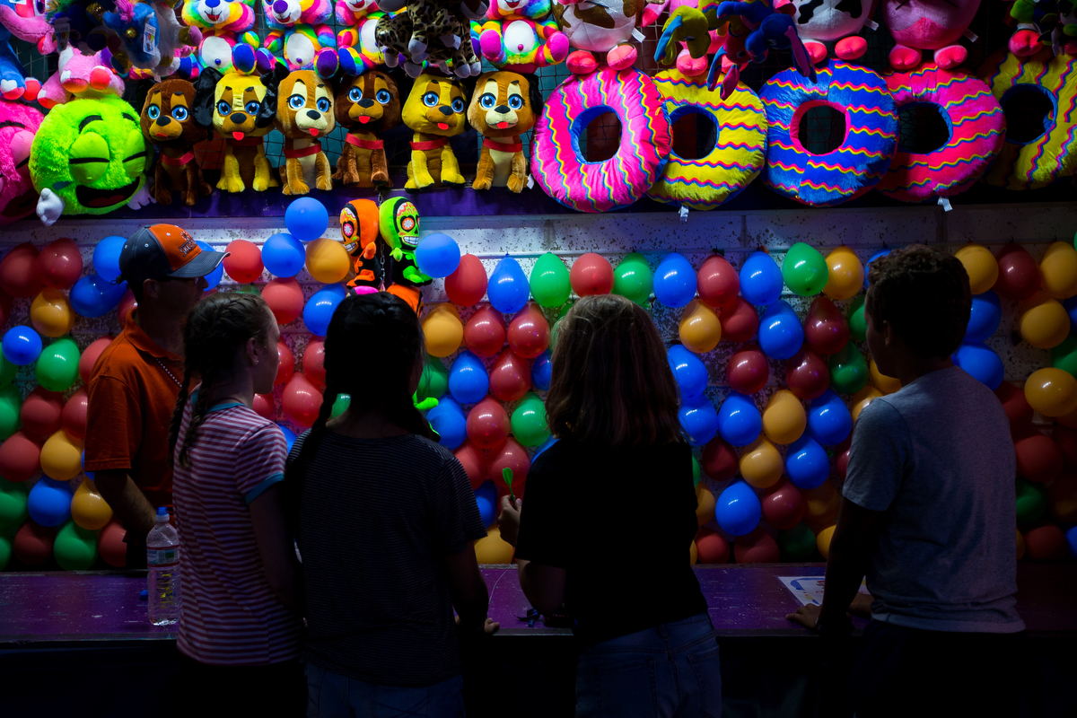 A group of people play a carnival game during the opening day of the Ann Arbor Jaycees Carnival at Huron high School on Wednesday, June 21, 2017. The carnival runs from Wednesday to Sunday and over 30 rides and carnival games are available for all ages. Matt Weigand | The Ann Arbor News