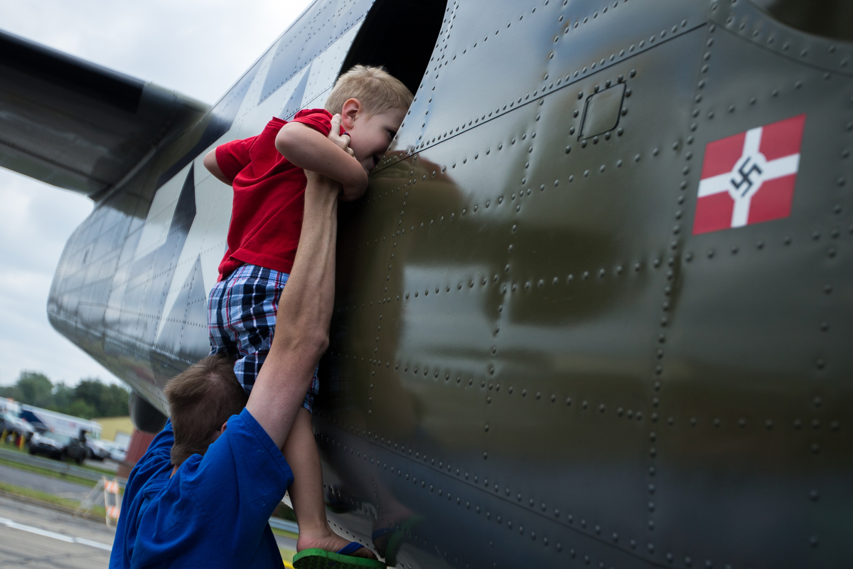 Joshua Dedinsky holds up his son Logan, 2, to look inside of an airplane at the Thunder Over Michigan Air Show at Willow Run Airport on Sunday, September 3, 2017. Matt Weigand | The Ann Arbor News