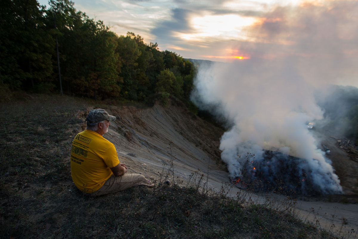 Barry Boyes watches as a large pile of wood chips burns along Toma Road in Dexter on Monday, October 2, 2017. The cause of the fire is not known, but it is expected to burn for days. Matt Weigand | The Ann Arbor News