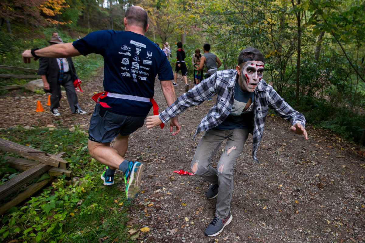 """Joey Markell chases runners at Nichols Arboretum for the first Zombie Run 2017 on Friday, October 13, 2017. The run was a 5K where participants ran with """"life"""" flags and about 50 zombies were hidden throughout the course attempting to take the flags. Runners who had flags remaining at the end of the run were entered into a raffle for gift cards and prizes. Matt Weigand 
