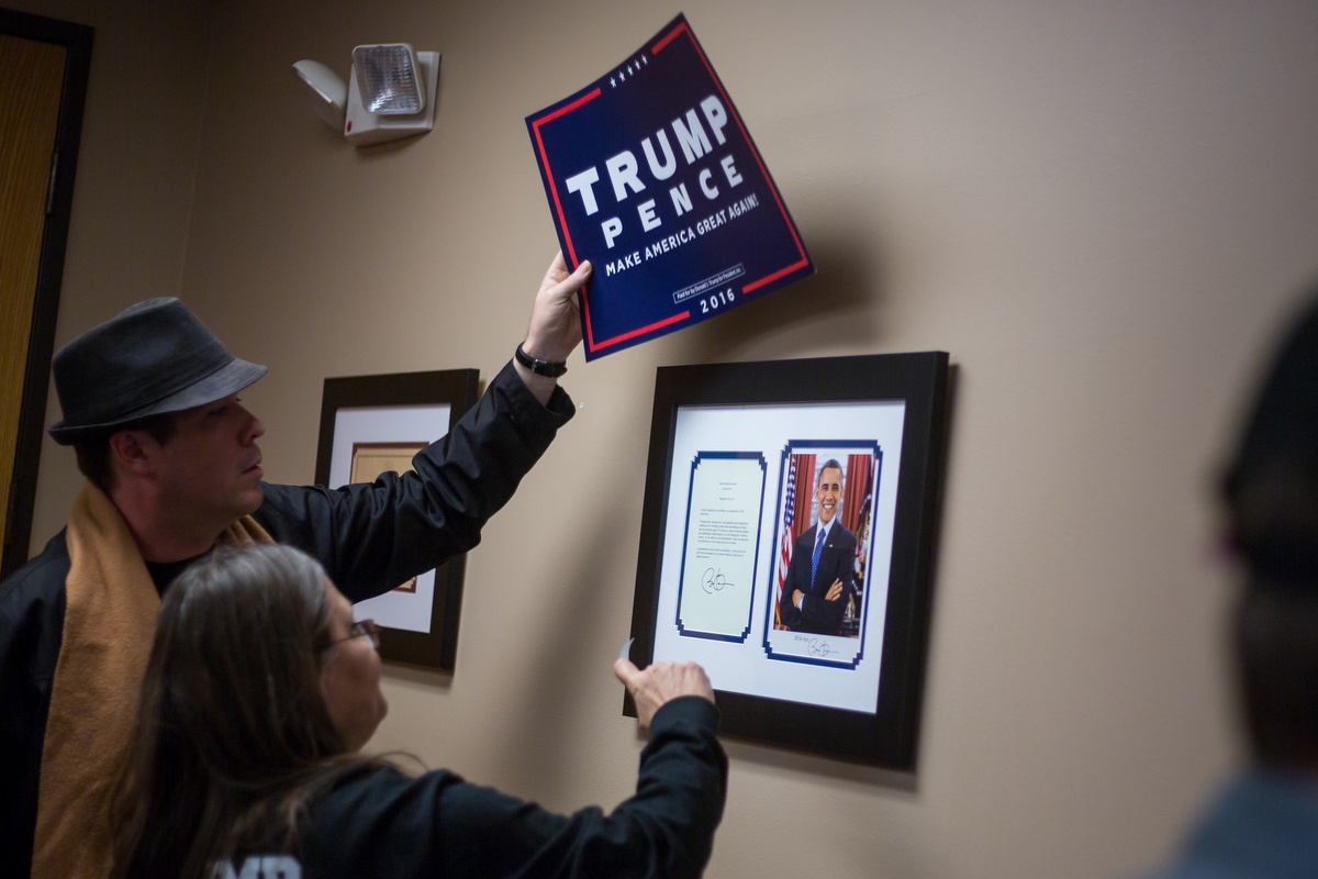 Deborah Fuqua-Frey, right and a man who did not disclose his name place a Donald Trump sign over a picture and letter form President Obama at the Washtenaw County Republicans watch party at the National Center for Manufacturing Sciences building on Tuesday, November 8, 2016. Roughly 30 people attended the event to watch the arrival of the electoral votes on Tuesday night. Matt Weigand | The Ann Arbor News