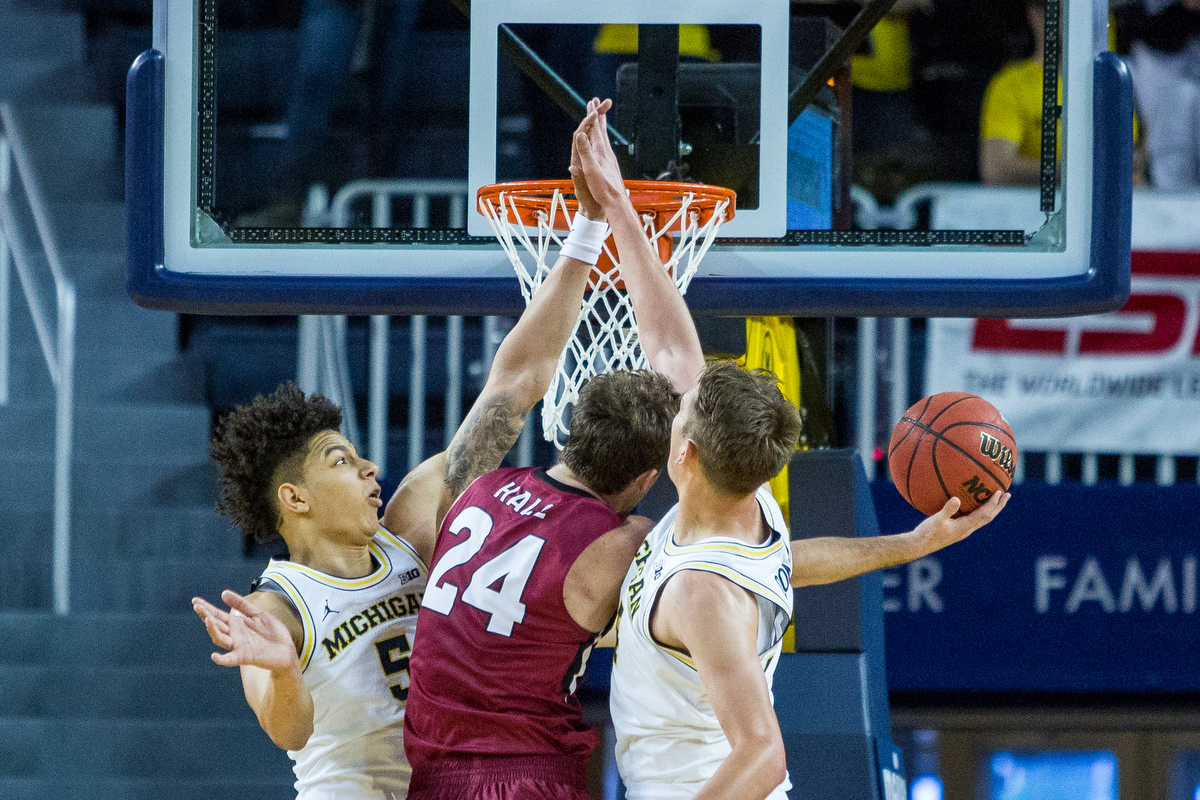 Michigan�s D.J. Wilson (5), left and Michigan�s Mark Donnal (34) foul IUPUI's Evan Hall (24) during the second half of play against IUPUI at the Crisler Arena on Sunday, November 13, 2016. The Michigan Wolverines beat the IUPUI Jaguars 77-65. Matt Weigand | The Ann Arbor News