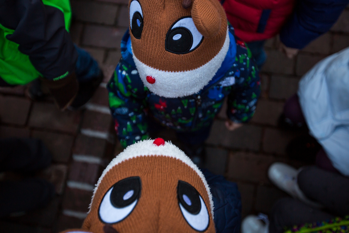 Lucas Ailuni, bottom, 2 and older brother Elias, 4, talk with each other while wearing Rudolph hats at the Kerrytown Christmas tree lighting on Sunday, November 27, 2016. The lighting, which took place at the Kerrytown Market and Shops, featured singing from the Pioneer High School choir, a tree lighting and a visit from Santa. Matt Weigand | The Ann Arbor News