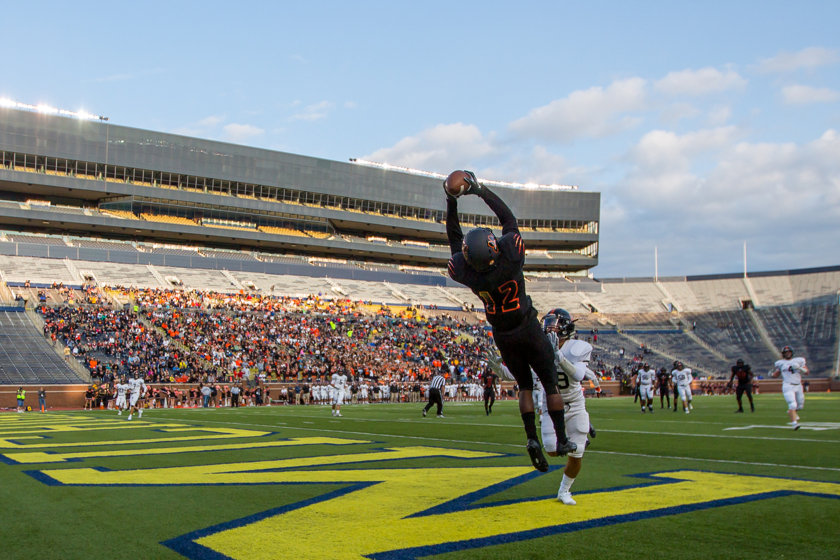 Belleville's Julian Barnett, 12, makes a jumping catch for a touchdown during the opening game of Battle at the Big House at Michigan Stadium on Thursday, August 24, 2017. The Belleville Tigers beat the Brighton Bulldogs 34-31 in overtime.