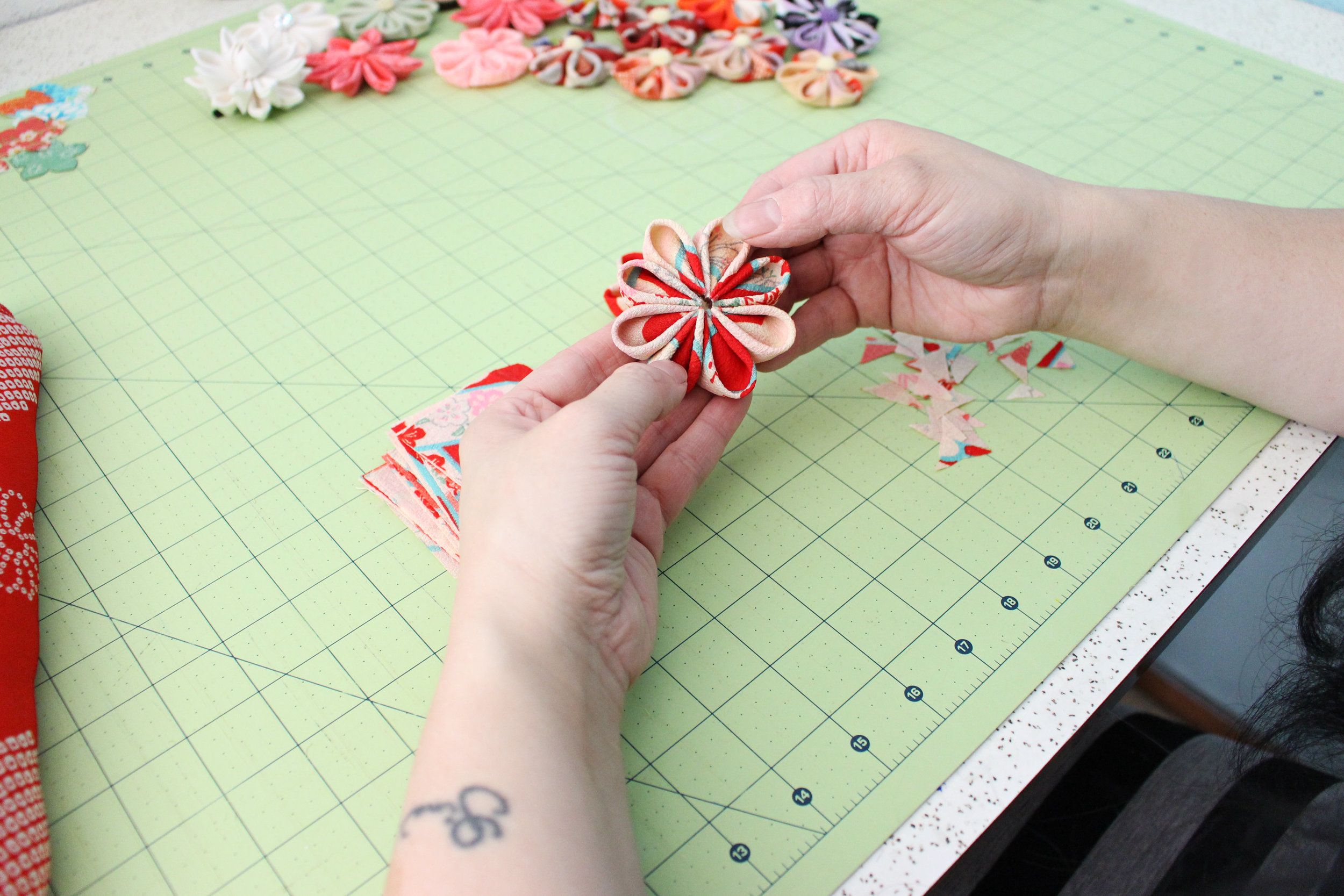 One by one. It's how I get the job done. I get a lot of amazed looks when I saw I hand fold every single petal. But after doing it this long I compare it to knitting for myself. I just get into my zone and fold, fold, fold.