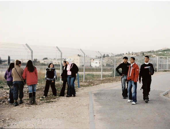The young journalists from Israel welcome the young journalists from the West Bank as they cross the checkpoint (2007). Dealing with reality is part of their routine, so is asking many questions about this reality.