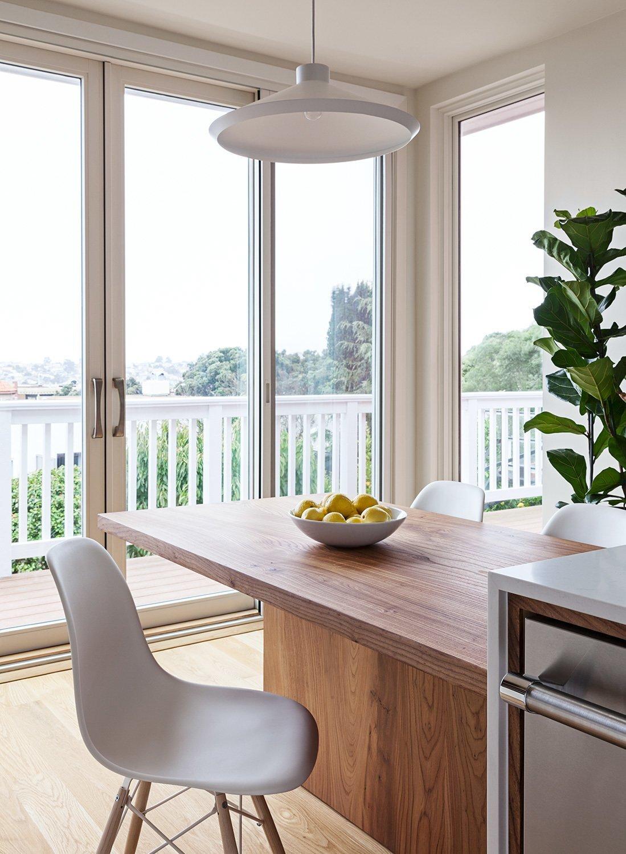floor-to-ceiling-windows-brighten-the-small-footprint-custom-elm-wood-table-by-kaimade 2.jpg